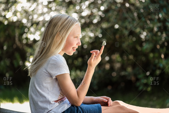 Girl looking at a small moth on her finger