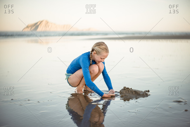Blonde girl digging in the sand on the beach