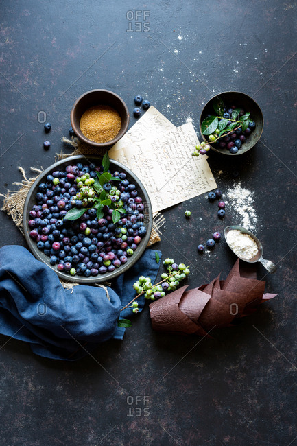Farm fresh blueberries and other ingredients on dark blue surface