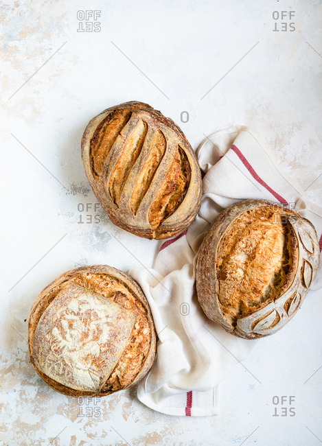 Three loaves of freshly baked homemade sourdough bread over light background top view