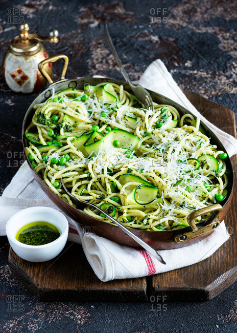 Spaghetti with peas, zucchini and pesto sauce in a vintage pot over dark background