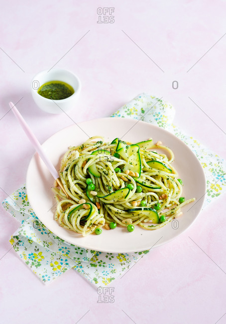 Spaghetti with peas, zucchini, pine nuts and pesto sauce in a plate over pink background
