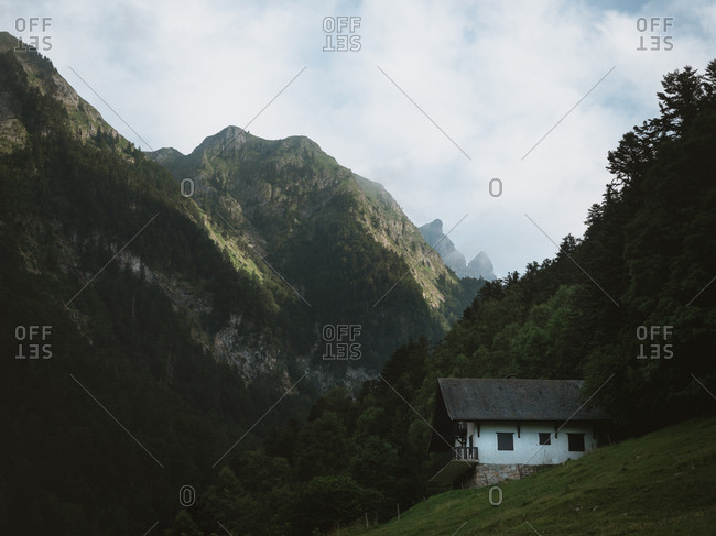 Small white house in a green hill with big mountains in the background