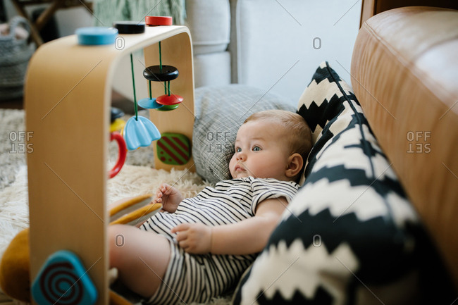 Baby lying on floor looking at hanging toy