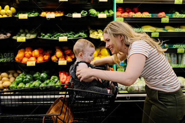 Mother and daughter grocery shopping for organic vegetables