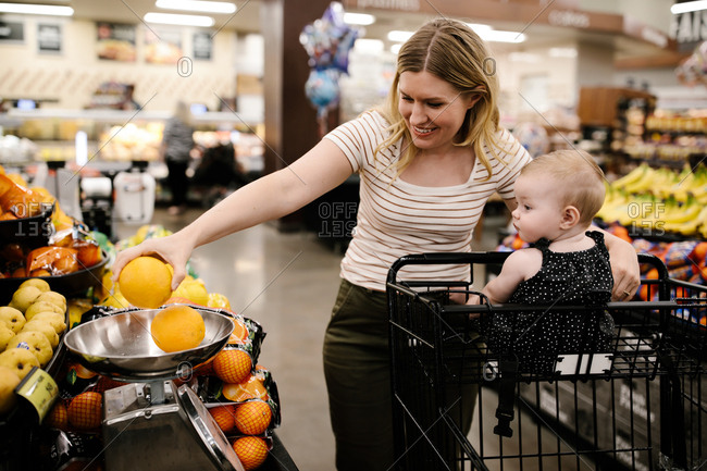 Mother and daughter grocery shopping for fresh fruit