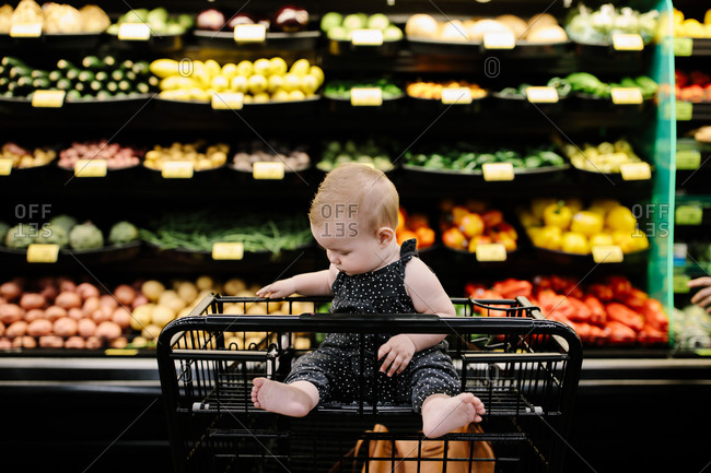 Baby in the organic produce section of a grocery store