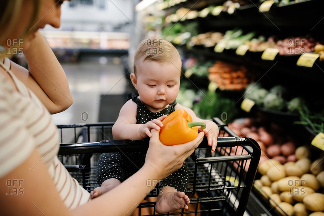 Mother and baby grocery shopping for organic produce