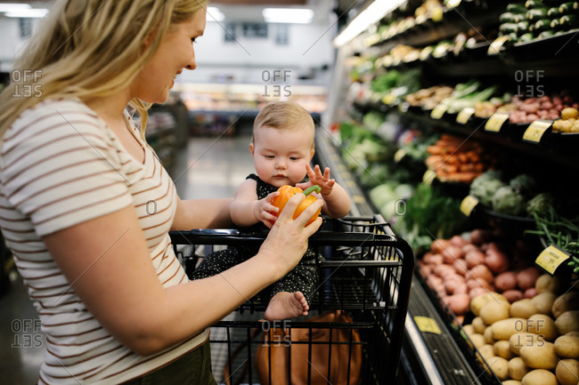 Mother and daughter grocery shopping for organic produce