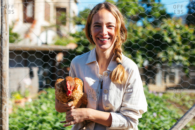 Caucasian woman carrying in her arms a chicken in a farm.