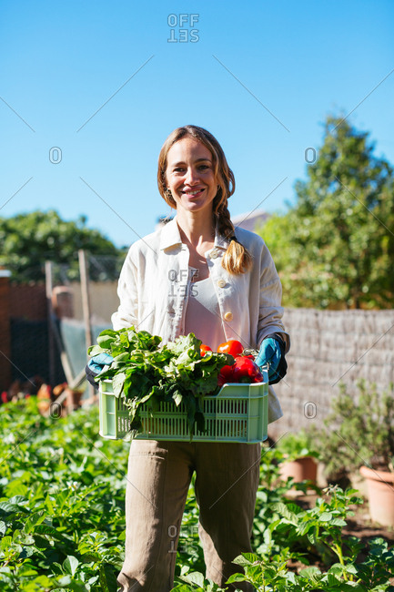 Caucasian woman holding a vegetable's basket in an ecological garden.