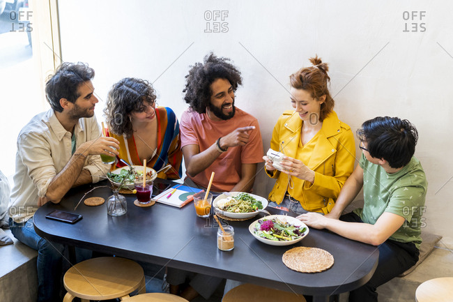 Group of happy friends with an instant camera having lunch in a restaurant