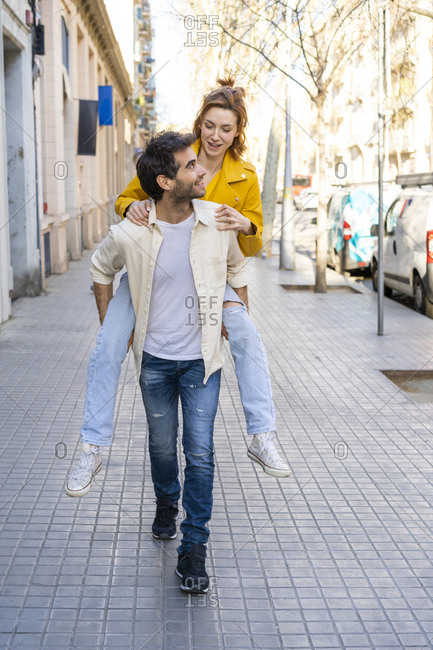 Man giving girlfriend a piggyback ride on pavement in the city