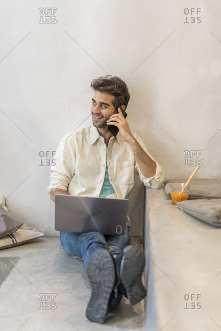 Man sitting on a step using cell phone and laptop