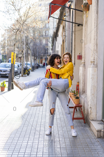 Carefree young woman carrying friend in the city