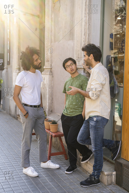 Three young men talking in the city