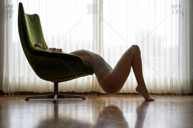 Young woman in a bodysuit posing in armchair at home