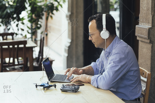 Businessman with headphones- laptop and drone in a coffee shop