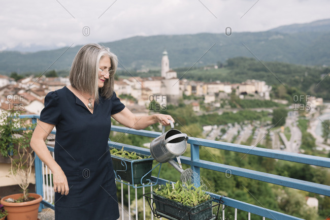 Smiling senior woman watering plants on her roof terrace- Belluno- Italy
