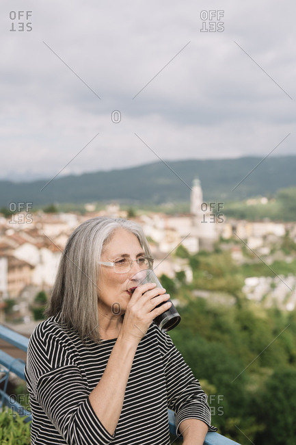 Portrait of senior woman drinking coffee on her roof terrace- Belluno- Italy