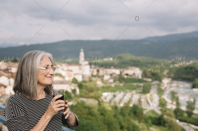 Relaxed senior woman with glass of coffee on her roof terrace- Belluno- Italy