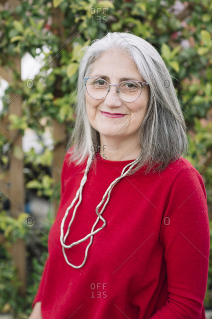 Portrait of smiling senior woman with grey hair wearing red pullover and glasses