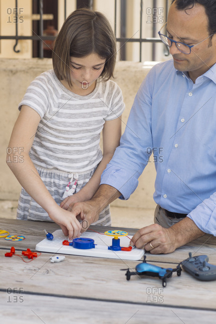 Father teaching his daughter electronics and robotics