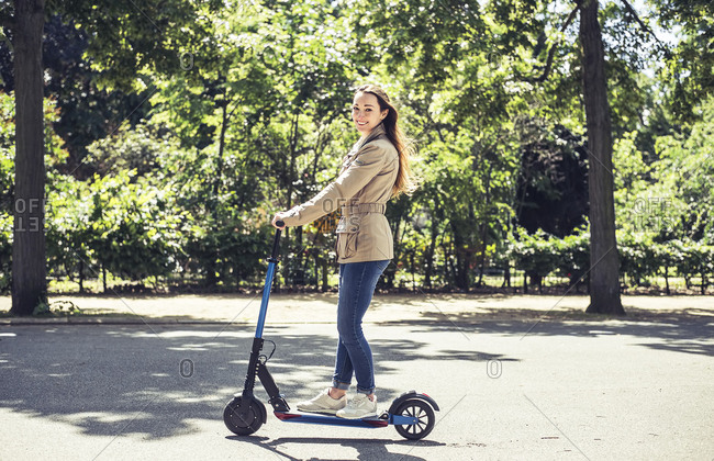 Portrait of smiling woman with E-Scooter