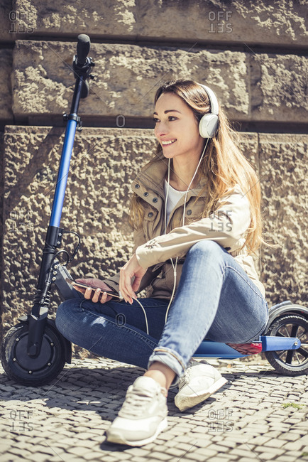 Smiling woman sitting on E-Scooter listening music with headphones and smartphone