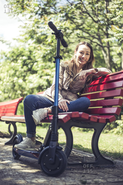 Portrait of smiling woman with E-Scooter relaxing on bench