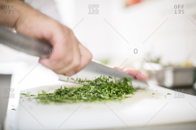 Cook chopping herbs
