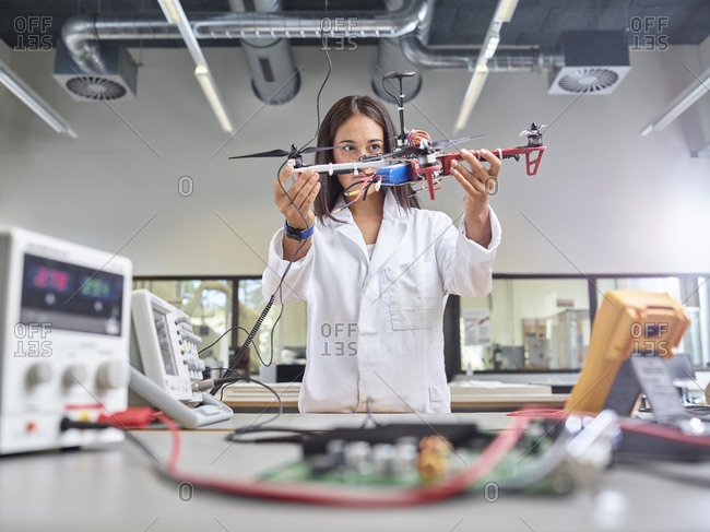 Female technician working in research laboratory- holding drone