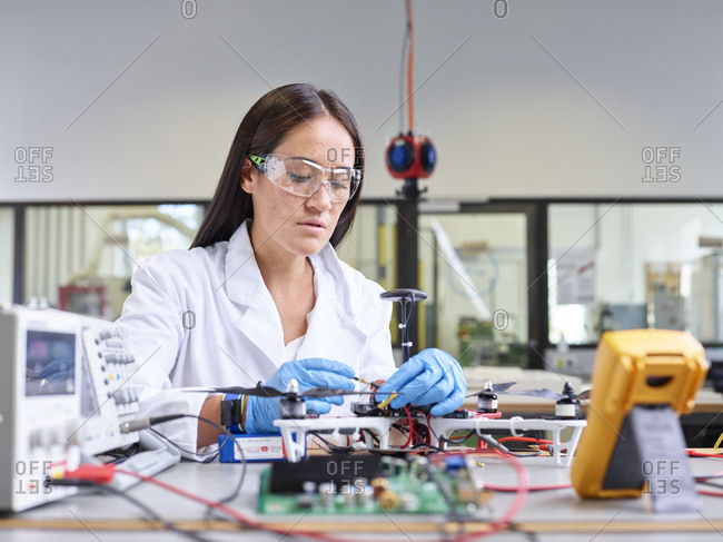 Female technician working in research laboratory- connecting plug of drone