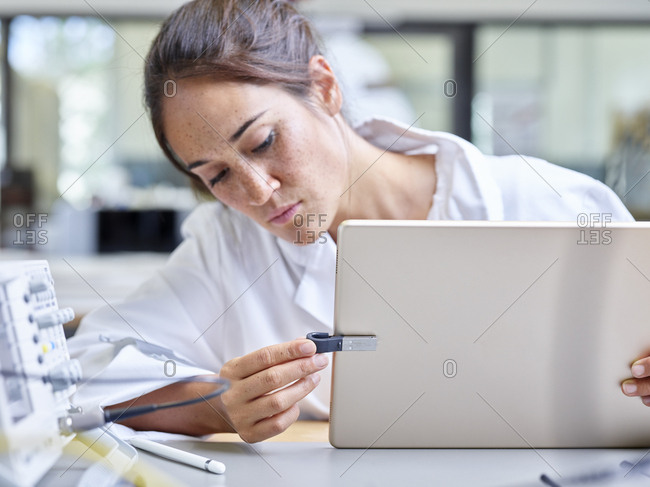 Female technician working in research laboratory- tablet and usb stick