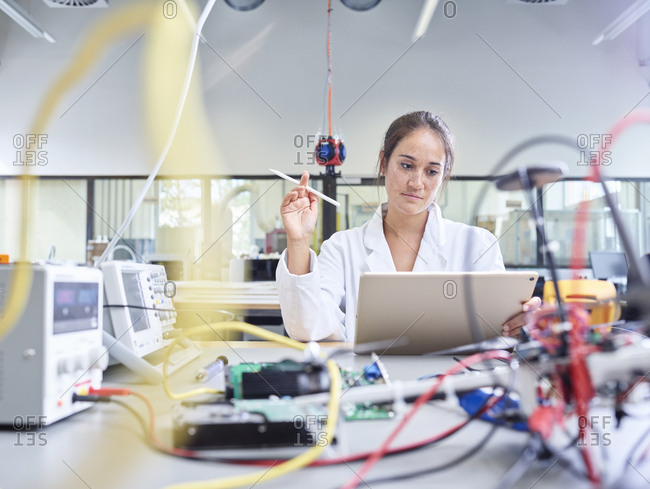 Female technician working in research laboratory- holding pencil in front of tablet