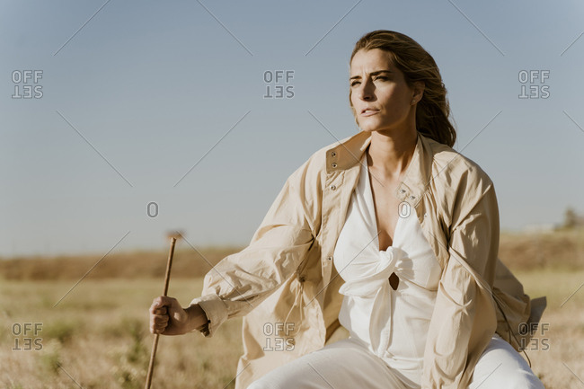 Female traveller sitting on stool- meadow