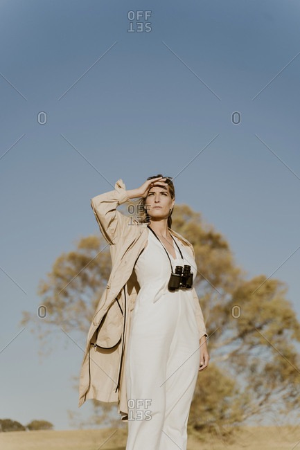 Female traveller with binoculars- hand on forehead