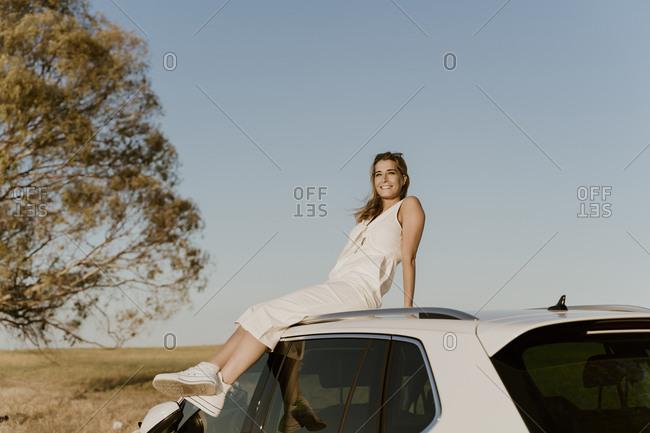 Female traveller sitting on white car roof