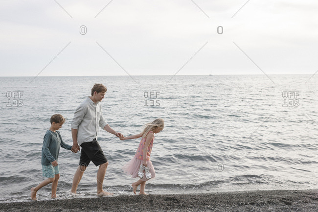 Father walking hand in hand with little daughter and son at seafront