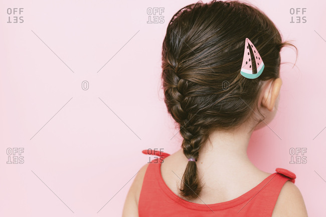 Back view of little girl with braid and hair clip against pink background