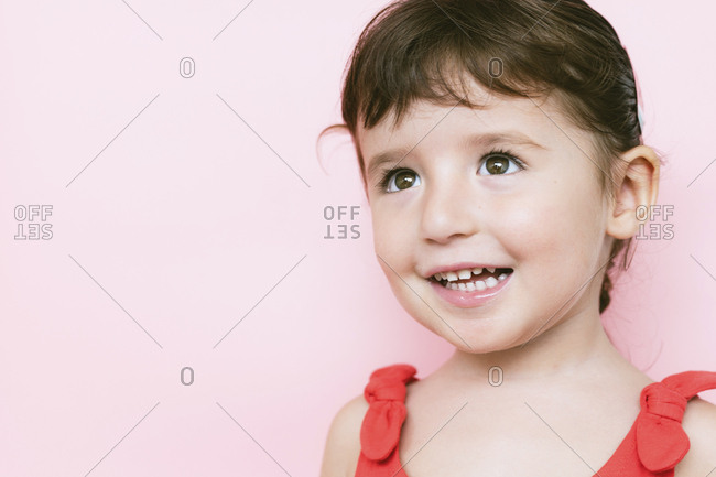 Portrait of smiling little girl in front of pink background looking up