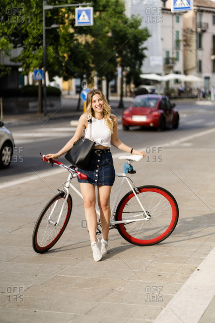 Portrait of happy young woman with racing cycle in the city
