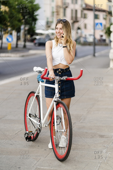 Portrait of smiling young woman with racing cycle on the phone