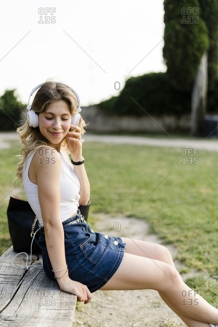 Portrait of relaxed young woman sitting on bench outdoors listening music with headphones