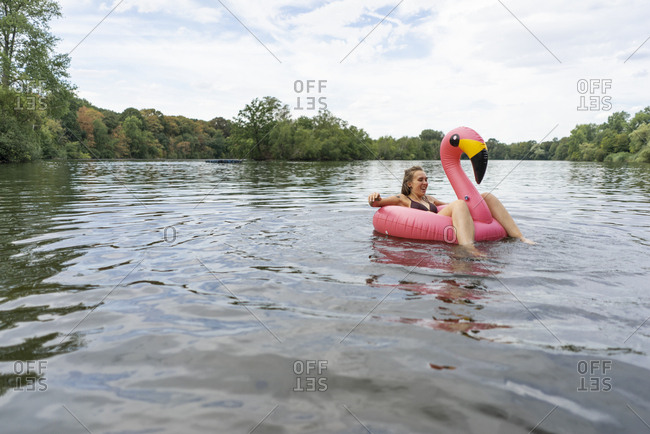 Young woman floating on a lake in a pink flamingo floating tire