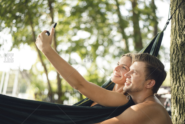 Couple relaxing in hammock by the lake- taking smartphone selfies