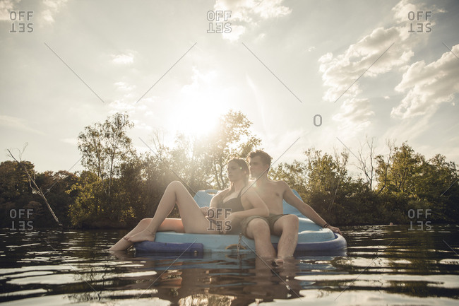 Young couple sitting on a boat on the lake- relaxing