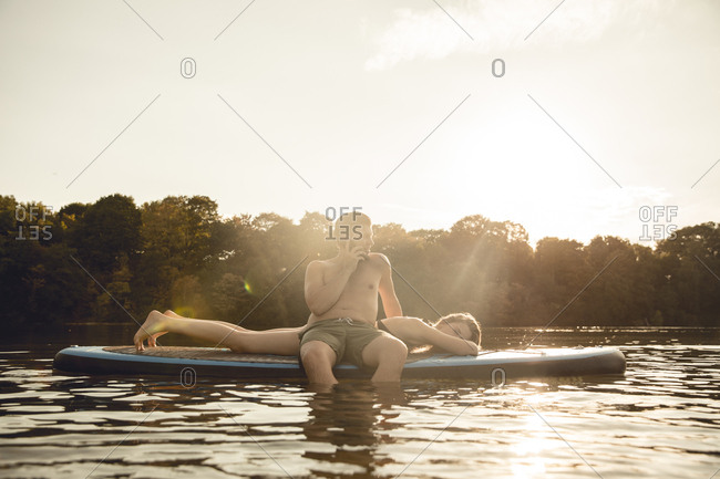 Youple on the lake- relaxing on a paddleboard- man talking on the phone