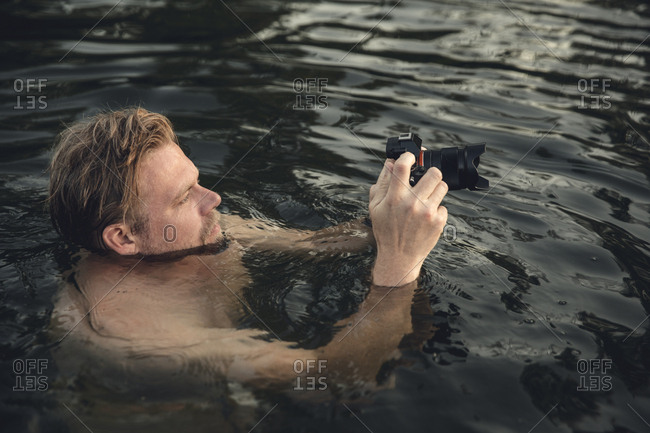 Man swimming in lake- take pictures with his camera