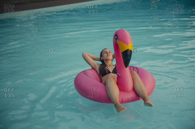 Young woman relaxing on a pink flamingo floating tire